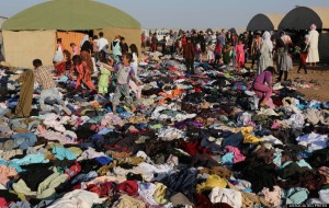 Displaced Ezidi people look for clothes at the Nowruz refugee camp in Derike, August 12, 2014. (AP Photo/ Khalid Mohammed).